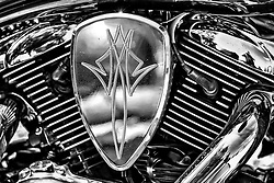 An Air Filter Emblem From A  2007 Kawasaki Vulcan 1600 with Chrome Details and Accents in Black and White. <br /> <br /> With a 95 cubic inch V-twin engine providing plenty of low-end torque and excellent highway muscle, the Vulcan 1600 Classic has extra power for just about anything its rider chooses to do. Of course, extra power is nice for playtime, but when a trip calls for extended seat-time, the single-pin crankshaft provides a comforting rhythm that isn't tarnished by harsh vibrations, thanks to the engine's gear-driven counter balancer.<br /> <br /> The design details that make the 1600 Classic a one-of-a-kind American classic include a wide, pullback handlebar, stepped seat, dual slash-cut mufflers, and a multi-reflector headlight. Features of the integrated instrument cluster include an LCD screen, tank-mounted ignition switch, fuel-injection warning lamp, fuel gauge, odometer, tripmeter and clock.