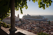 Seen from Miradouro de de Santa Luzia, the Independence of the Seas cruise liner dominates the medieval/Moorish district rooftops of Alfama, on 13th July 2016, in Lisbon, Portugal. Pollution from such huge ships is a toxic problem that is growing as the cruise industry and its ships get ever bigger, docking close to communities with narrow streets such as Lisbon. MS Independence of the Seas is a Freedom-class cruise ship operated by the Royal Caribbean cruise line which entered service in April 2008. The 15-deck ship can accommodate 4,370 passengers and is served by 1,360 crew.