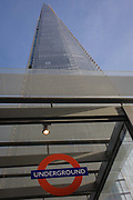 A London Underground sign is positioned beneath the tall architecture of The Shard at London Bridge. Looking upwards to the point of the Shard's pinnacle, we see the roof of an entrance to the Underground station a few metres from the London Bridge mainline station, a transport hub and gateway to the City of London and Southwark on the Southbank. Standing 306 metres (1,004 ft) high, the Shard by Italian architect Renzo Piano is currently the tallest building in the European Union. It dominates this borough of Southwark in south London.