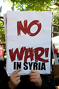Demonstration against any intervention in Syria called by Stop the War and CND, August 30th 2013, Central London. A woman hides her face behind a placard saying 'No war in Syria'.