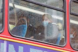 © Licensed to London News Pictures. 13/05/2021. London, UK. A woman wearing a face covering travelling on a bus in north London. It has been reported that government officials are discussing ending coronavirus face covering rules and only making masks mandatory on public transport by the end of June. The next stage of the Covid-19 lockdown easing takes place from Monday 17 May, allowing people to hug and return to mixing indoors in pubs and restaurants. Photo credit: Dinendra Haria/LNP