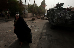 A woman walks through a residential the street of in Ahdamiyah - a largely Sunni district in central Baghdad - on the first morning of a large-scale security sweep by US and Iraqi soldiers and police on Sunday August 27, 2006. The sweep is being led by the 172nd Stryker Brigade based in Fairbanks, Alaska. The 172nd was extended at the last moment - with portions of the brigade already back in the States - when they were called upon to bolster security forces in Baghdad seeking to get a handle on a massive wave of sectarian killings in the Iraqi capital.