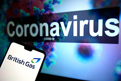 The British Gas logo seen displayed on a mobile phone with an illustrative model of the Coronavirus displayed on a monitor in the background. Photo credit should read: James Warwick/EMPICS Entertainment