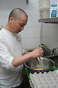 A Cook beating eggs