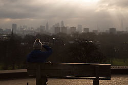 Primrose Hill, London, February 15th 2015. A woman takes in the view of London's skyline as the sun breaks through the clouds on a chilly early morning on Primrose Hill, overlooking London's skyline.<br /> ///FOR LICENCING CONTACT: paul@pauldaveycreative.co.uk TEL:+44 (0) 7966 016 296 or +44 (0) 20 8969 6875. ©2015 Paul R Davey. All rights reserved.