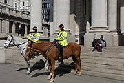 Mounted City Police officers make their presence known while on their horses in spring sunshine at Royal Exchange in the heart of the capitals financial district, on 19th April, in the City of London, England.