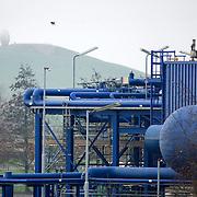 Nederland Barendrecht 29 november 2008 20081129 Foto: David Rozing ..TOT 6 DECEMBER GEEN PUBLICATIE VAN DEZE BEELDEN ..Serie demonstratie project ondergrondse Co2 opslag Shell Barendrecht.NAM in Barendrecht. Op het terrein staat een gaswinninginstallatie, hiermee wordt het gas dat zich onder Barendrecht bevindt naar boven gehaald. Zodra de 2 gasvelden leeg zijn zullen deze waarschijnlijk gebruikt gaan worden voor de ondergrondse opslag van CO2. Dit gebeurt met dezelfde installatie. .Shell Nederland Raffinaderij B.V. (SNR) heeft het initiatief genomen voor een demonstratieproject in samenwerking met Nederlandse Aardolie Maatschappij ( NAM ). Daarbij is het de bedoeling dat pure CO2 die bij de raffinaderij in Pernis bij de productie van waterstof vrijkomt, per pijpleiding naar Barendrecht wordt getransporteerd. Vervolgens wordt de CO2 in lege aardgasvelden geïnjecteerd voor permanente opslag..OCAP?De Shell exploiteert momenteel de nu nog deels gevulde aardgasvelden Barendrecht en Ziedewij en heeft een grote kennis van de ondergrond en injectie van aardgas in bestaande velden.Het is de bedoeling dat OCAP ook het transport van CO2 naar Barendrecht gaat verzorgen..Shell CO2 Storage B.V.?Voor het project is een nieuw bedrijf opgericht, Shell CO2 Storage B.V. (SCS). SCS zal verder ook zekerstellen dat alle aanwezige kennis over de Barendrechtse velden ten volle kan worden benut bij de opslag van CO2 en de daaraan gekoppelde monitoring.Het Barendrecht-veld?Shell en OCAP hebben net zoals andere organisaties veel onderzoek gedaan naar het transport naar en de mogelijke CO2-opslag in lege aardgasvelden. Vanwege de ligging, dichtbij de CO2-bron van Pernis, hebben de partijen uiteindelijk gekozen voor het aardgasveld Barendrecht (ten zuidwesten van Rotterdam). Als de ervaringen met het Barendrecht-veld goed zijn, zal in een later stadium Barendrecht Ziedewij het tweede veld zijn dat in aanmerking komt voor CO2-opslag. Uit deze aardgasvelden wordt nu nog gas gewonnen. Zodra de pr