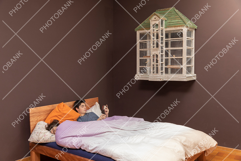 Boy in bed with his sleeping girlfriend and he looks at the phone