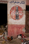 A cock struts under the detail of an old Coca-Cola mural on a wall at the weekly market at Qurna, a village on the West Bank of Luxor, Nile Valley, Egypt.   Arabic writing is above the famous brand name showing the cultures that the US company's presence reaches.