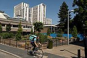 Deliveroo rider in the University grounds looking towards the Code student living building in an area under redevelopment in the East of the city on 23rd June 2021 in Coventry, United Kingdom. The UK City of Culture is a designation given to a city in the United Kingdom for a period of one year. The aim of the initiative, which is administered by the Department for Digital, Culture, Media and Sport. Coventry is a city which is under a large scale and current regeneration.