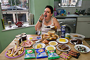 Jill McTighe, a mother and school aide, with a day's worth of food on a bingeing day, in her kitchen in Willesden, northwest London, United Kingdom.  (From the book What I Eat: Around the World in 80 Diets.) MODEL RELEASED. [Use of Jill McTighe images must be used contextually only and use cleared with Peter Menzel Photography on a case by case basis.]