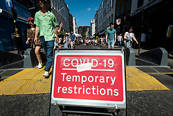 © Licensed to London News Pictures. 12/06/2021. LONDON, UK. People pass a Covid-19 temporary restrictions sign in Soho.  Scientific advisers to the UK government have called for a delay to the complete lifting of coronavirus lockdown restrictions on 21 June, possibly by four weeks, to allow scientists to assess the link between rising numbers of Covid-19 cases (mainly the newly identified Delta variant) and hospital admissions.  Photo credit: Stephen Chung/LNP