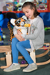 © Licensed to London News Pictures. 08/11/2017. London, UK. A young girl plays with FurReal Roarin' Tyler which is part of the Dream Toys top twelve toys for Christmas 2017. Photo credit: Ray Tang/LNP