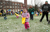 Savannah Shaw is able to find plenty of colored eggs scattered on the snow covered lawn at Laconia Rotary Park Saturday afternoon for the Easter Eggstravaganza event.  (Karen Bobotas/for the Laconia Daily Sun)