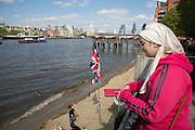 Union Jack flag flies over the River Thames beach on the Southbank, London, UK. At low tide this sandy area becomes almost like a coastal gathering spot with people using the water's edge as if the seaside. The South Bank is a significant arts and entertainment district, and home to an endless list of activities for Londoners, visitors and tourists alike.