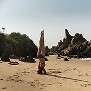 Woman does a head stand on a beach.
