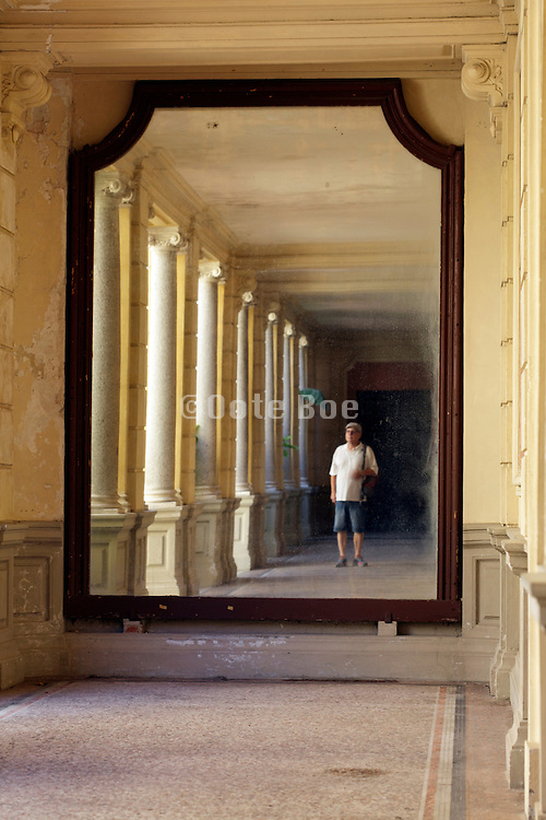 large mirror in classic hallway with person standing