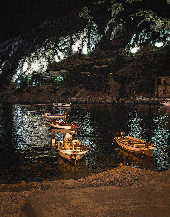 Small boats in the lagoon with lighted mountainside in the background