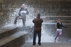 """© Licensed to London News Pictures. 09/11/2015. Bridlington, UK. FRAME 6 OF 9. A man poses for a photograph on the sea defences at the sea side town of Bridlington & gets caught out by a huge wave. The Yorkshire region was hit by severe gales this afternoon with winds up to 60mph. The Met Office warned West Yorkshire to expect gales and locally severe gales over high ground, with some """"very gusty"""" winds to the east of high ground as well.<br /> Photo credit: Andrew McCaren/LNP"""