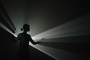 """© Licensed to London News Pictures. 29/01/2013. London, UK A woman moves in the light of Anthony McCall's """"You and I, Horizontal (2005) a solid light installation. Press preview of """"Light Show"""" at the Hayward Gallery at the Southbank Centre in London today 29th January 2013. The exhibition runs 30th Jan-28th Apr 2013. Photo credit : Stephen Simpson/LNP"""