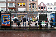 In Utrecht schuilen reizigers bij de bushalte tegen de stromende regen.<br /> <br /> In Utrecht travelers are seeking shelter at a bus stop for the pouring rain.