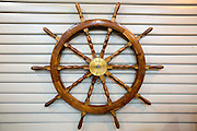 Wooden ship's wheel attached to a white wall outside the Mary Rose Museum in the Historic Naval Dockyard Portsmouth, Hampshire, UK.  The ancient wheel was part of the steering mechanism, know as the helm.