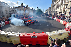 "© Licensed to London News Pictures. 12/07/2017. London, UK.   A driver performs a ""doughnut"" during a parade of Formula One cars taking place around a circuit passing Trafalgar Square and Whitehall during a promotional event called F1LiveLondon ahead of the British Grand Prix at Silverstone.   Photo credit : Stephen Chung/LNP"