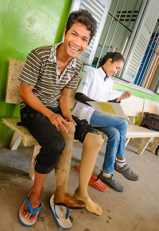 Teenage boy who received a prosthetic leg after he stepped on a landmine is fitting a new leg adjusted for his growth. Physical Rehabilitation Center, Siem Reap, Cambodia. Photo © Robert van Sluis