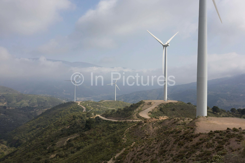 """Wind farm uprights and turbine blades perch on the hilltop of Sierra Nevada foothills near the spa town of Lanjaron, Andalucia. From a higher vantagepoint, looking downhill into a distant valley, we see four turbines turning on a re-landscaped hill with ditant could shroud the lower slopes of the Sierra Nevada mountain range. According to information provided by the regional government's """"Andalusian Energy Agency"""" (Agencia Andaluza de la Energía), 31.8 percent of this region's energy will come from renewable energy in 2013. That is equivalent to 90% of home energy consumption in the south of Spain."""
