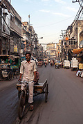 A porter cycles his rickshaw through Chandni Chowk in Old Delhi, India, at first light. It is one of the oldest and busiest markets in Old Delhi and was built in the seventeenth century by the Mughal Emperor Shah Jahan.