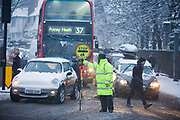 In the morning rush-hour, a busy road junction is seen during a snow-shower as traffic builds up at traffic lights and pedestrians to and fro in Dulwich Village, Southwark, South London. Snowflakes can be picked out in car headlights as a lollypop man in fluorescent yellow holds his stop sign to waiting cars, eager to get on with their journeys across the capital during bad weather at the start of 2010, A Mini still has a thick layer of snow on its roof and bonnet (hood) and a number 37 bus to Putney Heath has passengers on its top deck, steamed up in the chilly temperature outside and the warm moisture inside.  On the far right is a grey GATSO traffic camera that flashes those who jump red lights. For those struggling to reach work or school, this is another challenging commuting morning.