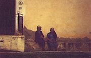 Two eldery Italian women sit on the side of a downtown street