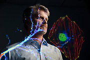 Scott Soderling, a research professor in the department of cell biology, poses in his lab with projected images from his research