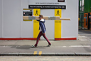 South London youth walks past the site entrance of the regeneration project at Elephant & Castle, London borough of Southwark.