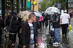 © Licensed to London News Pictures . 09/07/2016 . Manchester , UK . An umbrellas salesman on Market Street in Manchester City centre as persistent , heavy rain leads to flooding of roads and tramways in Manchester City Centre . Photo credit : Joel Goodman/LNP