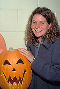 Woman leader age 23 with pumpkin at youth Halloween party.  St Paul  Minnesota USA
