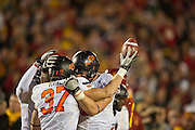 Nov 18, 2011; Ames, IA, USA; Oklahoma State Cowboys linebacker Alex Elkins (37) holds up the football while surrounded by teammates during the second half of a game against the at Jack Trice Stadium. Iowa State Cyclones defeated the Oklahoma State Cowboys 37-31. Mandatory Credit: Beth Hall-US PRESSWIRE Editorial sports photography of the Iowa State Cyclones vs. Oklahoma State Cowboys in 2011 in Aimes, Iowa.