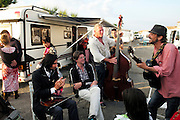 """Volkskrant journalist Peter Giesen with Yardani to his right, listens to gypsy music in a Manouche camping site on the outskirts of Saintes Maries de la Mer<br /><br />""""Le Pelerinage des Gitans""""; the French gypsy pilgrimage of Saintes Maries de la Mer, Camargue, France<br /><br />Sainte Sara is an uncannonized saint, who legend says looked after the Christian Saints Marie Jacobe and Marie Salome, cousins of Mary Magdalene, who arrived, it is said, on the shores of the Camargue in a rudderless boat. Saint Sara is the patron saint of gypsies who come from far and wide to see her. There are even paintings of Sara as 'Kali' the black saint in Eastern Europe. Sara may have been the priestess of 'Ra' the sun-god or even servant girl to the Christian saints. No-one really knows.<br /><br />For a few weeks of the year, Roma, Gitan and Manouche gypsies come from all over Europe in May, camping in caravans around Saintes Maries de la Mer. It is a festive time where they play music, dance, party and christen their children. They all go to see Saint Sara in the crypt, kissing or touching her forehead. Many put robes on her shoulders, making her fat for the procession. In the main Gypsy procession of the 24th May, Saint Sara is allowed to leave her crypt, beneath the church, and is carried from the church to the shores of the mediterranean and back again. One day a year she is free from her prison. Hundred's of years ago the Gypsies used not even to be allowed into the church, only into the crypt like Sara...<br /><br />Roma gypsies still suffer oppressive prejudice and racism and are one of the ethnic groups the most persecuted and marginalised across Europe. The festival is one of the times where they celebrate with people of all races, their faith and traditions"""
