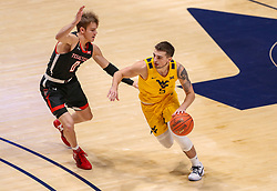 Jan 25, 2021; Morgantown, West Virginia, USA; West Virginia Mountaineers guard Jordan McCabe (5) dribbles while defended by Texas Tech Red Raiders guard Mac McClung (0) during the first half at WVU Coliseum. Mandatory Credit: Ben Queen-USA TODAY Sports