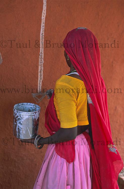 Inde, Rajasthan, Village des environs de Tonk, cette femme realise des peintures murales (Thapa) sur le mur exterieur de sa maison. // India, Rajasthan, village around Tonk, woman painting her house wall (thapa)