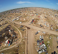 A pile of destroyed cars of teachers (lower) sits outside Briarwood elementary school in Oklahoma City, Oklahoma May 22, 2013.  Rescue workers with sniffer dogs picked through the ruins on Wednesday to ensure no survivors remained buried after a deadly tornado left thousands homeless and trying to salvage what was left of their belongings. Curvature of horizon in the photo is due to an ultra-wide angle lens.  REUTERS/Rick Wilking (UNITED STATES)