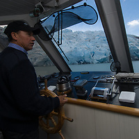 A tour boat captain navigates in Grey Lake, below the calving front of Grey Glacier in Torres del Paine National Park, Chile.