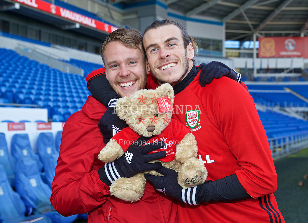 CARDIFF, WALES - Friday, November 11, 2016: Wales' Chris Gunter and Gareth Bale pose for a photograph with Fraser Bear, a mascot for the Believe charity promoting organ donation, during a training session at Cardiff City Stadium ahead of the 2018 FIFA World Cup Qualifying Group D match against Serbia. (Pic by David Rawcliffe/Propaganda)