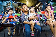 27 APRIL 2013 - BANGKOK, THAILAND:  Children watch a Chinese opera performance in the Talat Noi neighborhood of Bangkok's Chinatown. Chinese opera was once very popular in Thailand and is usually performed in the Teochew language. Millions of Chinese emigrated to Thailand (then Siam) in the 18th and 19th centuries and brought their cultural practices with them. Recently its popularity has faded as people turn to performances of opera on DVD or movies. There are as many 30 Chinese opera troupes left in Bangkok. They travel from Chinese temple to Chinese temple performing on stages they put up in streets near the temple, sometimes sleeping on hammocks they sling under their stage. The opera troupes are paid by the temple, usually $700 to $1000 a night.  PHOTO BY JACK KURTZ