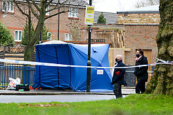 © Licensed to London News Pictures. 20/01/2021. London, UK. Detective officers walks past a police tent on West Green Road in Haringey, north London as police launch a murder investigation following the fatal stabbing of a teenage boy in Haringey. Police were called at 21:10hrs on Tuesday 19 January 2021 to the West Green Road junction with Willow Walk, following reports of a stabbing. Officers attended with the London Ambulance Service and found a male, aged 17, suffering from a stab injury. The victim was pronounced dead at 04:25hrs on Wednesday 20 January. . Photo credit: Dinendra Haria/LNP