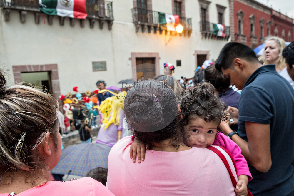 A young child is scared by the procession of Giant paper mache puppets in a fiesta procession through the city at the start of the week long fiesta of the patron saint Saint Michael September 22, 2017 in San Miguel de Allende, Mexico.