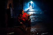 26th November 2015, New Delhi, India.  A woman sweeps the floor in the ruins of Feroz Shah Kotla in New Delhi, India on the 26th November 2015<br /> <br /> PHOTOGRAPH BY AND COPYRIGHT OF SIMON DE TREY-WHITE a photographer in delhi<br /> + 91 98103 99809. Email: simon@simondetreywhite.com<br /> <br /> <br /> The13th century fortress-city of Firoz Shah Kotla in Delhi is thronged weekly with thousands of supplicants seeking favour from supernatural beings of smokeless fire, - Djinns. These magical entities also known as Jinn, Jann or Genies spring from Islamic mythology as well as pre-Islamic Arabian mythology. They are mentioned frequently in the Quran and other Islamic texts and inhabit an unseen world called Djinnestan. Believers, mostly Muslim but from other faiths too, circumnavigate the ruins clutching dozens of photocopied requests, flower petals, incense, and candles. They visit the numerous niches and alcoves in the catacombs said to be occupied by different djinns and greet and salute the invisible occupants with offerings.  A copy of their requests, often with detailed contact information, photographs and even police reports to bolster the case is left with the 'Baba' before moving on to the next where the procedure is repeated - like making applications at different departments of a bureaucracy