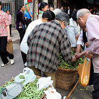 Asia, China, Chongqing. Locals select fresh beans in the street market in Chongqing.