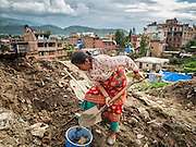 02 AUGUST 2015 - BHAKTAPUR, NEPAL:   A woman digs up dirt for her temporary shelter in a small Internal Displaced Person (IDP) camp in Bhaktapur. Bhaktapur was badly damaged in the earthquake the hit Nepal in April 2015. The Nepal Earthquake on April 25, 2015, (also known as the Gorkha earthquake) killed more than 9,000 people and injured more than 23,000. It had a magnitude of 7.8. The epicenter was east of the district of Lamjung, and its hypocenter was at a depth of approximately 15 km (9.3 mi). It was the worst natural disaster to strike Nepal since the 1934 Nepal–Bihar earthquake. The earthquake triggered an avalanche on Mount Everest, killing at least 19. The earthquake also set off an avalanche in the Langtang valley, where 250 people were reported missing. Hundreds of thousands of people were made homeless with entire villages flattened across many districts of the country. Centuries-old buildings were destroyed at UNESCO World Heritage sites in the Kathmandu Valley, including some at the Kathmandu Durbar Square, the Patan Durbar Squar, the Bhaktapur Durbar Square, the Changu Narayan Temple and the Swayambhunath Stupa. Geophysicists and other experts had warned for decades that Nepal was vulnerable to a deadly earthquake, particularly because of its geology, urbanization, and architecture.      PHOTO BY JACK KURTZ