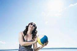 Mature woman playing volleyball on the beach, Bavaria, Germany